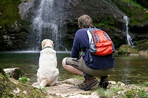 man-and-dog-sitting-by-waterfall